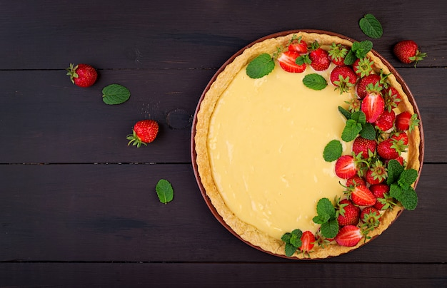 Tart with strawberries and whipped cream decorated with mint leaves on dark table. top view