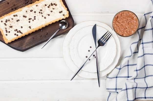 Тарт с ванильным кремом или чизкейк с шоколадными каплями и чашкой кофе на белом деревянном столе,