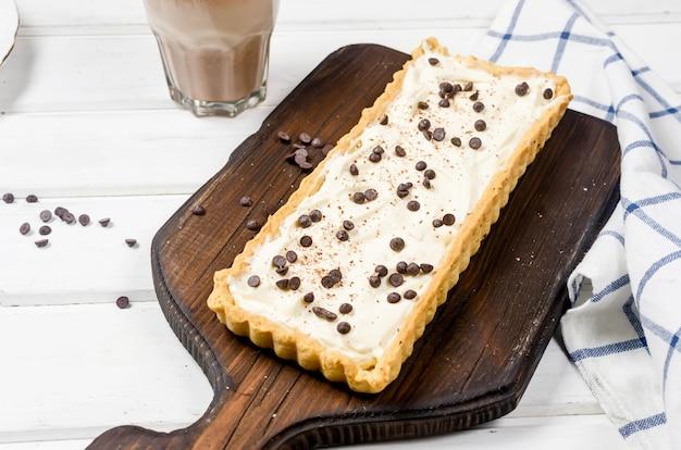 Тарт с ванильным кремом или чизкейк с шоколадными каплями и чашкой кофе