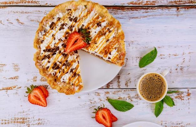 Пирог со взбитыми сливками и чашечкой кофе на белой деревянной поверхности. вид сверху.