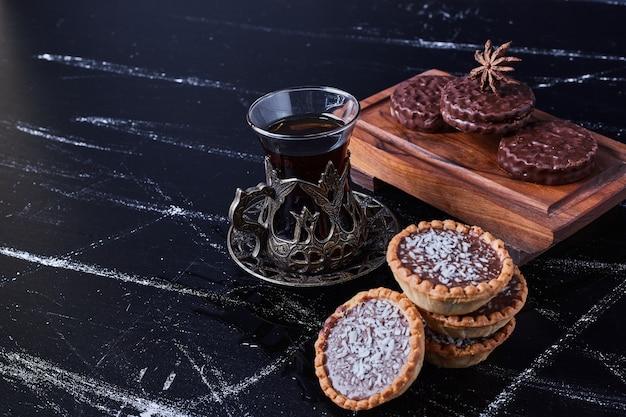 Tartalette con crema al cioccolato servite con un bicchiere di tè.