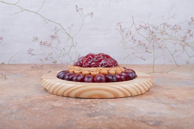 Тарталетки с конфитюром из кизила и ягодами на деревянной тарелке