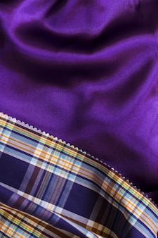 Tartan pattern textile on smooth purple fabric