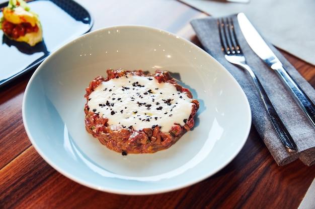 Тартар, холодная закуска из сырого мяса или рыбы, политая сливками и сливочным соусом, лежит на белом ...