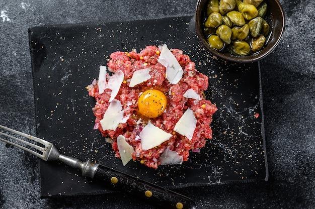 ウズラの卵、ケッパー、パルメザンチーズを添えたタルタルビーフ。黒の背景。上面図。