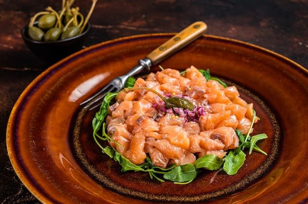 연어 생선, 적 양파, 아루 굴라, 케이 퍼를 소박한 접시에 담은 타르타르 또는 타르타르. 평면도.