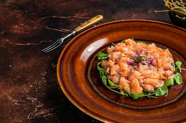 소박한 접시에 연어 생선, 붉은 양파, 아루굴라, 케이퍼를 곁들인 타르타르 또는 타르타르