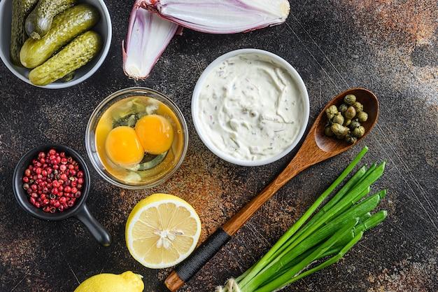 Соус тартар в миске с органическими ингредиентами из классического рецепта сверху на деревенской поверхности темного металла.