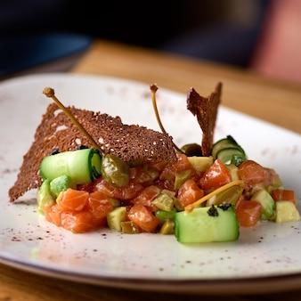 Тартар. салат с копченым лососем и огурцом на деревянном столе