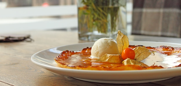 Tarte tatin with apples and ice cream decorated with cape gooseberry