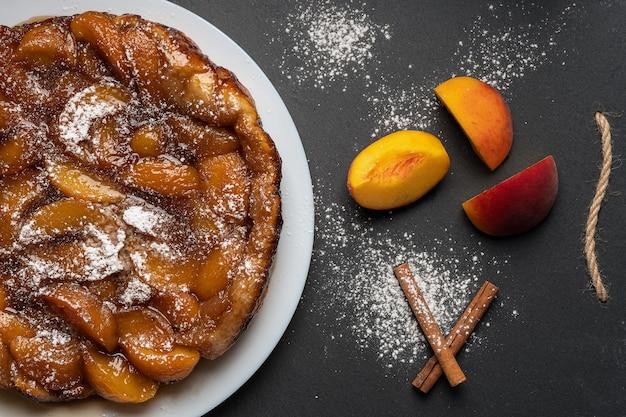 近くの暗い背景に白い皿に桃のキャラメルと粉砂糖を入れたタルトタタン