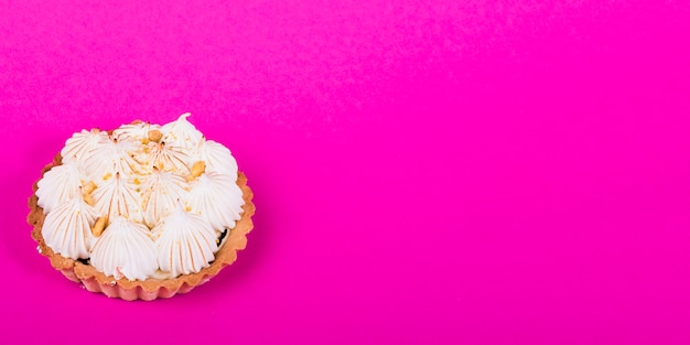 Tartlet with italian meringue against pink background