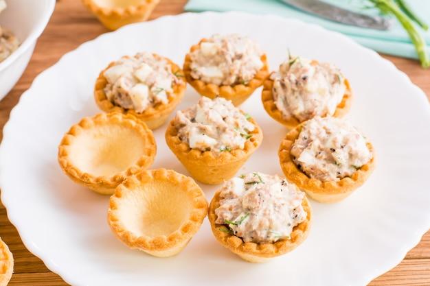 Tartlets는 비어 있으며 접시에 생선과 계란 샐러드가 가득합니다