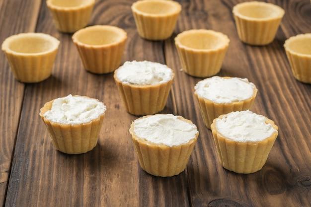 タルトは空で、木製のテーブルにカッテージチーズが入っています。おいしいおやつを作る過程。
