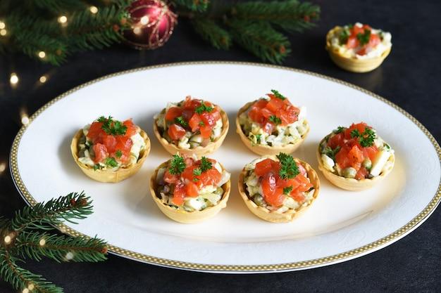 새해 테이블에 샐러드와 연어로 채워진 타 틀릿. 샴페인 한 잔과 함께 축제 테이블