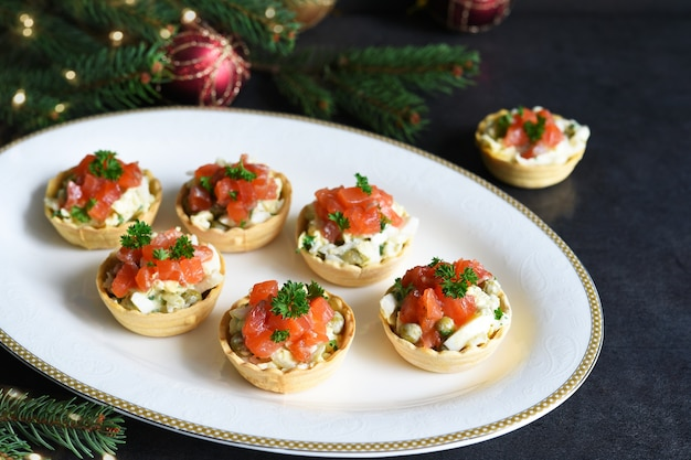 Tartlets stuffed with salad and salmon on a new year's table. festive table with a glass of champagne