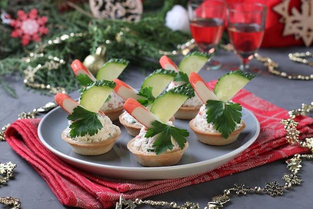灰色の背景のプレートにカニカマ、クリームチーズ、キュウリのタルト。お正月のおやつ。水平フォーマット。閉じる。