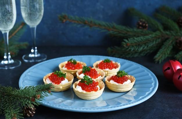 Тарталетки со сливочным сыром и красной икрой на красивой тарелке на рождественском столе.