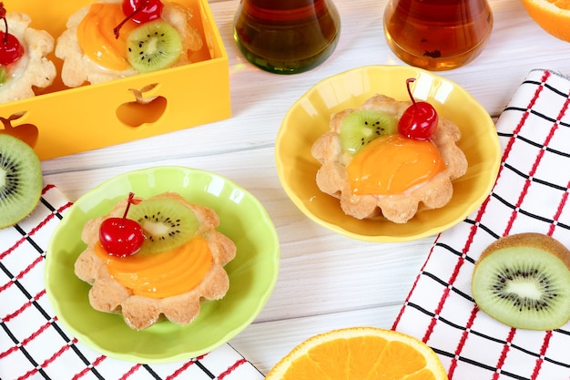 白い木製のテーブルの上の果物とお茶のタルト