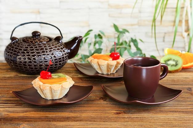 木製のテーブルにフルーツとお茶のタルト