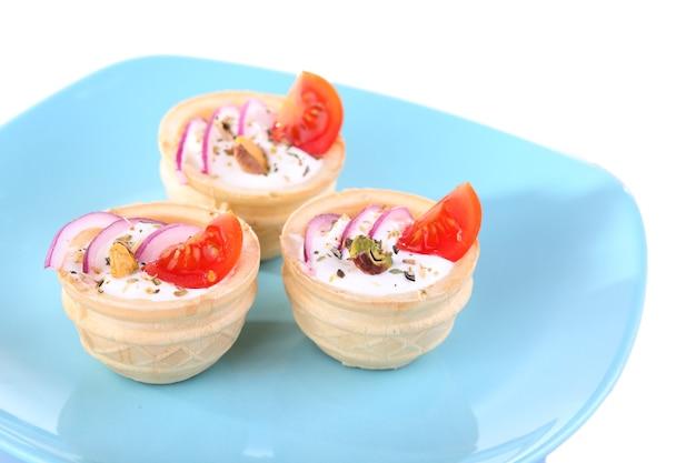 Тарталетки с зеленью и овощами с соусом на тарелке крупным планом