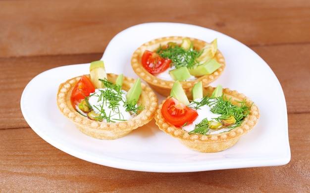 Тарталетки с зеленью и овощами с соусом на тарелке на столе