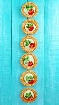 Тарталетки с зеленью и овощами с соусом на столе крупным планом