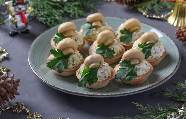 짙은 회색 배경에 버섯, 계란, 치즈를 넣은 타르트. 맛있는 명절 간식.