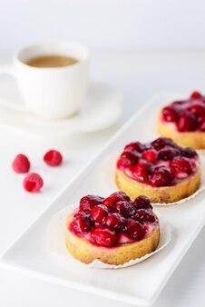 Тарталетки с малиной и чашка кофе на белом фоне.