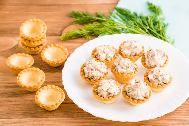 Tartlets with salad from fish and eggs on a plate and empty tartlets on a table