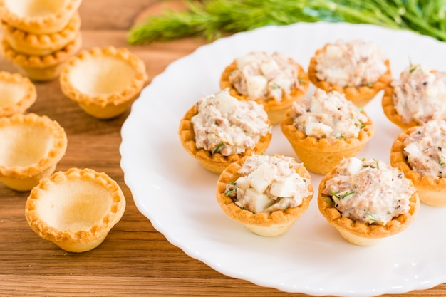 Tartlets with salad from saury and eggs on a plate and empty tartlets on a table