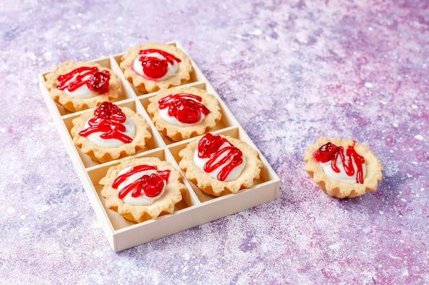 Тарталетки с начинкой из белого шоколада и сверху ягодным вареньем.