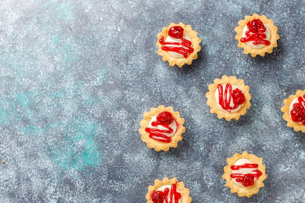 Tartlets with white chocolate filling and berry jam on top.