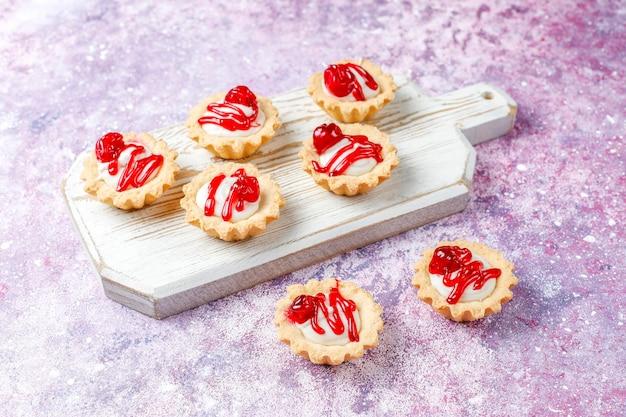 Tartellette con ripieno di cioccolato bianco e confettura di frutti di bosco sopra. Foto Gratuite