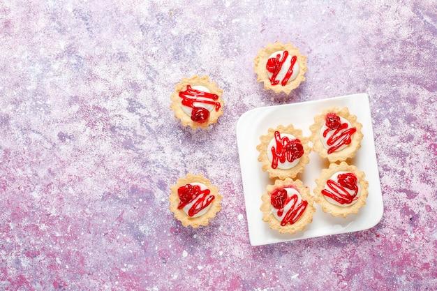 Tartellette con ripieno di cioccolato bianco e confettura di frutti di bosco sopra.
