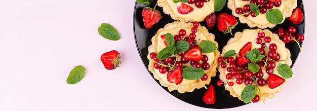 Tarts with strawberries, currant and whipped cream decorated with mint leaves. banner. top view