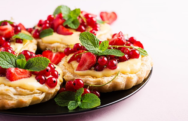 Tarts with strawberries, currant and whipped cream decorated with mint leaves