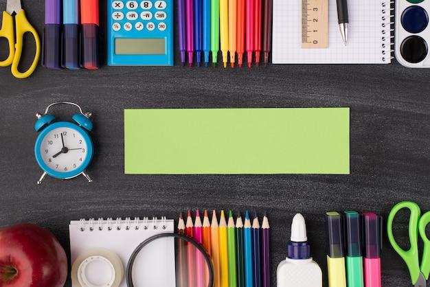 タスクの期限の概念。学校プロジェクトのコンセプト。上部にある時計の俯瞰写真の横に緑色のメモがあり、その上下にカラフルな文房具がコピースペース付きの黒板に分離されています