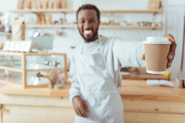 それを味わいます。喫茶店のカウンターの近くに立っているうれしそうな若いバリスタの手にある一杯のコーヒーに焦点が当てられています