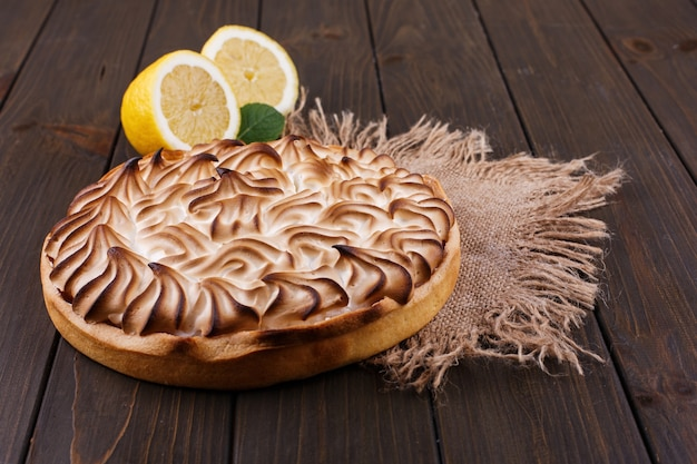 Tasteful lemon pie with white cream served on wooden table