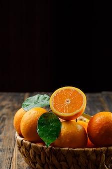 Вкусные апельсины в плетеной корзине с листьями