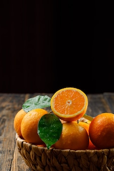 Tasteful oranges in a wicker basket with leaves
