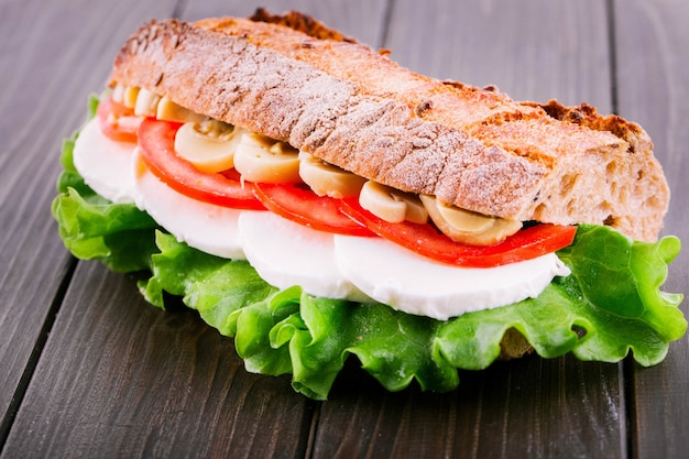 Tasteful sandwich made of sliced mushrooms, tomatoes, boiled eggs and salad