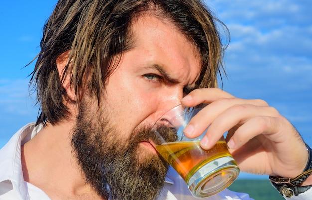 テイスティングとデグステーション。コニャックを飲むひげを生やした男。ブランデーのガラスを持つハンサムな男。