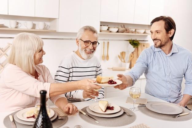 おいしい母親のケーキを味わう。夕食を食べ、母親からデザートのプレートを手に入れながら、先輩の両親と週末を楽しんでいる笑顔の嬉しい成熟した男