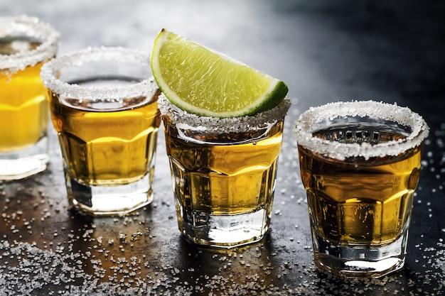 Вкусный алкогольный напиток коктейль текила с известью и солью на ярком темном фоне. крупный план. горизонтальный.