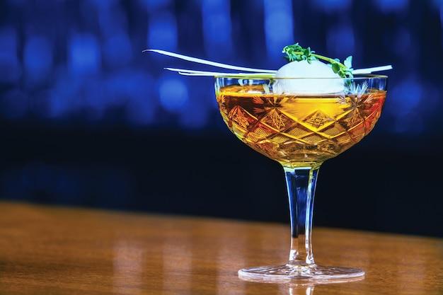 내부에 큰 얼음 공과 허브가 있는 맛있는 알코올 음료. 세련된 유리에 제공됩니다.