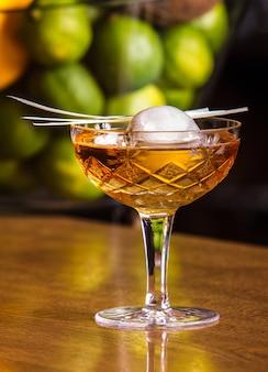 안에 큰 얼음 공이 있는 맛있는 알코올 음료. 육즙이 풍부한 라임을 배경으로 세련된 유리잔에 제공됩니다.