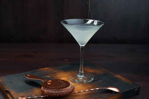 ヴィンテージのバースプーンとストレーナーの隣のテーブルには、エレガントなグラスにテキーラを入れたおいしいアルコールカクテル「マルガリータ」があります。プロのカクテルの準備。