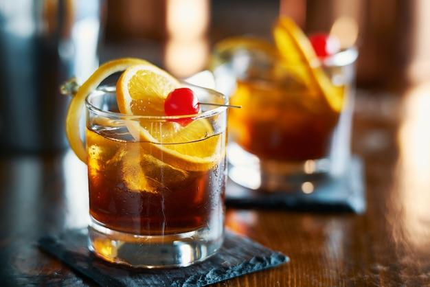 オレンジスライス、チェリー、レモンの皮の付け合わせで美味しいアルコールの昔ながらのカクテル